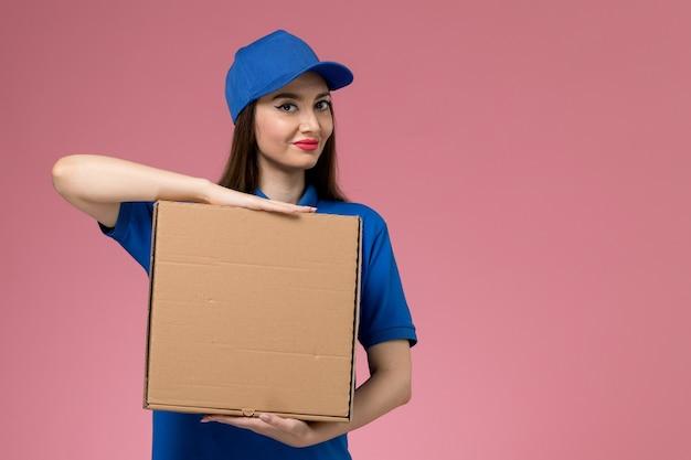Jovem mensageira de frente com uniforme azul e capa segurando uma caixa de entrega de comida sorrindo na parede rosa claro
