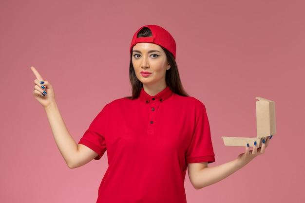 Jovem mensageira de frente com uniforme vermelho e capa com um pequeno pacote de entrega de comida nas mãos na parede rosa claro