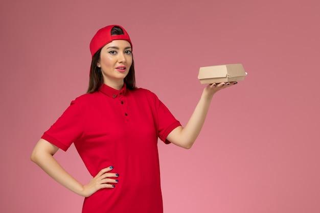 Jovem mensageira de frente com uniforme vermelho e capa com um pequeno pacote de entrega de comida nas mãos na parede rosa