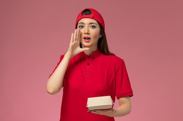 Jovem mensageira de frente com uniforme vermelho e capa com um pequeno pacote de entrega de comida nas mãos, no serviço de entrega de uniforme rosa