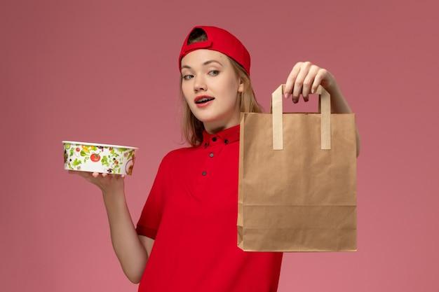 Jovem mensageira de frente com uniforme vermelho e capa segurando pacote de comida de entrega e tigela na mesa rosa entrega uniforme de trabalho