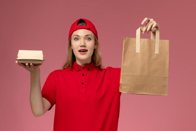 Jovem mensageira de frente com uniforme vermelho e capa segurando pacotes de comida de entrega na parede rosa