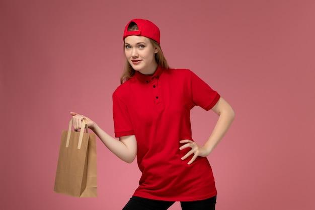 Jovem mensageira de frente com uniforme vermelho e capa segurando um pacote de comida de entrega na parede rosa