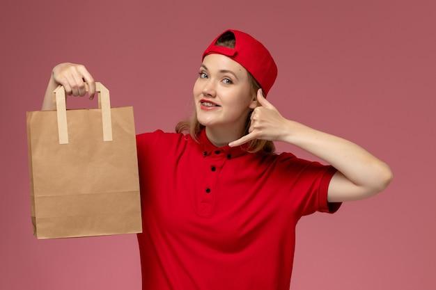 Jovem mensageira de frente com uniforme vermelho e capa segurando um pacote de comida para entrega, sorrindo na parede rosa