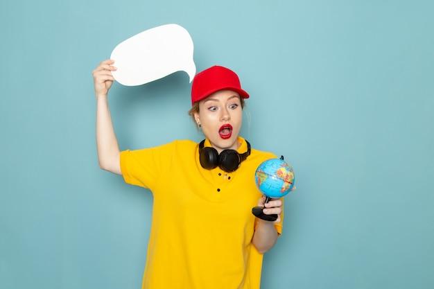 Jovem mensageira de frente para a mulher de camisa amarela e capa vermelha segurando um globo e uma placa branca no espaço azul