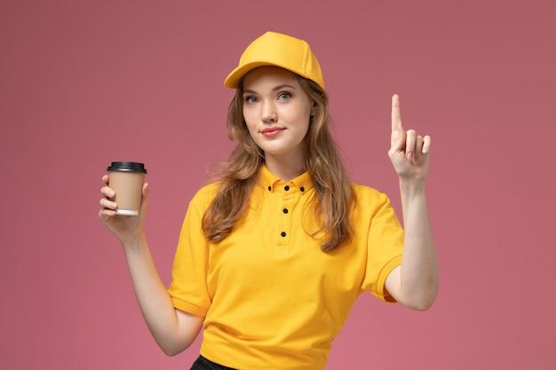 Jovem mensageira de uniforme amarelo segurando café e sorrindo na mesa rosa. trabalhador de serviço de entrega de uniforme de trabalho