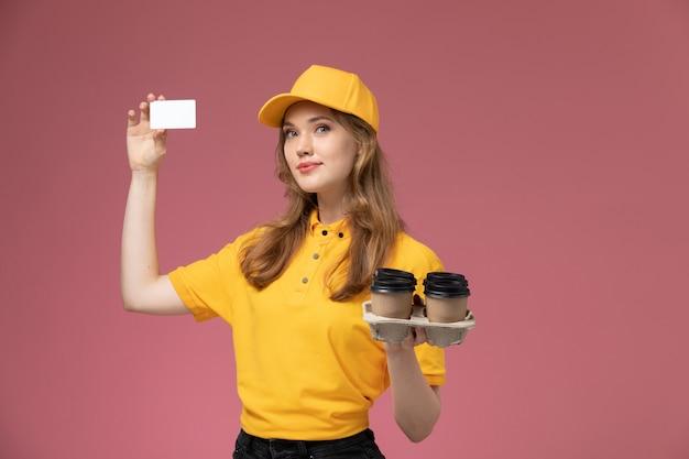 Jovem mensageira de uniforme amarelo segurando copos de plástico de café marrom com cartão na mesa rosa-escuro uniforme de serviço de entrega