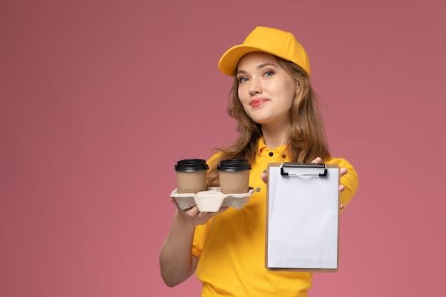 Jovem mensageira de uniforme amarelo segurando copos de plástico de café marrom com o bloco de notas na mesa rosa-escuro. serviço de entrega de uniforme