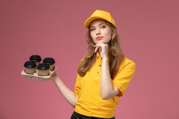 Jovem mensageira de uniforme amarelo segurando copos de plástico de café marrom pensando na mesa rosa-escura de frente para o serviço de entrega de uniforme.