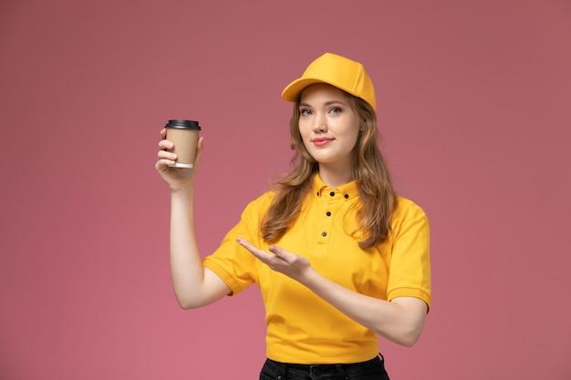Jovem mensageira de uniforme amarelo segurando uma xícara de café marrom na mesa rosa-escura de frente para o serviço de entrega de uniforme.