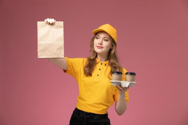Jovem mensageira de uniforme amarelo segurando xícaras de café e um pacote de comida na mesa rosa escura. trabalho de entrega uniforme.