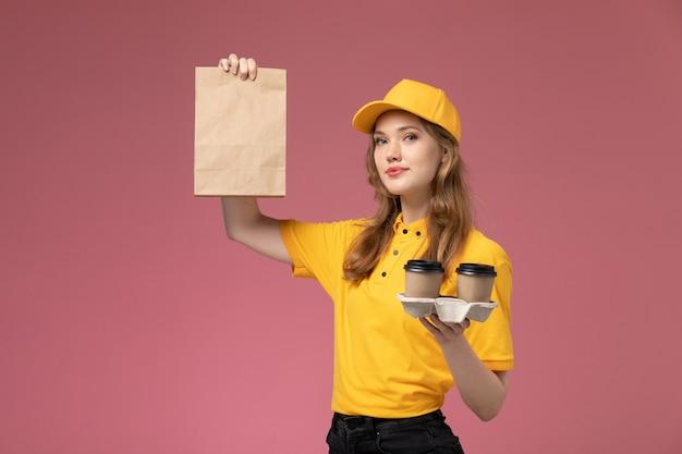 Jovem mensageira de uniforme amarelo segurando xícaras de café junto com um pacote de comida na mesa rosa escuro. trabalho de entrega uniforme.