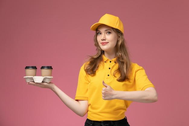 Jovem mensageira de uniforme amarelo segurando xícaras de café marrons na mesa rosa. trabalho de entrega uniforme.
