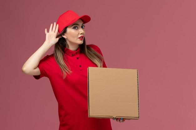 Jovem mensageira de uniforme vermelho segurando uma caixa de entrega de comida de frente, tentando ouvir no fundo rosa empresa de uniforme de entrega de serviço