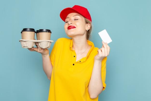 Jovem mensageira feminina de camisa amarela e capa vermelha de frente segurando copos de café de plástico e cartão branco no espaço azul