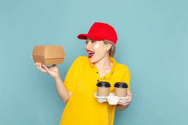 Jovem mensageira feminina de camisa amarela e capa vermelha de frente segurando xícaras de café de plástico e um pacote de comida no espaço azul