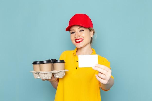 Jovem mensageira feminina de camisa amarela e capa vermelha de frente segurando xícaras de café de plástico no espaço azul.
