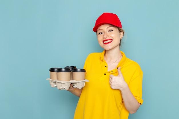 Jovem mensageira feminina de camisa amarela e capa vermelha de frente segurando xícaras de café de plástico sorrindo no espaço azul