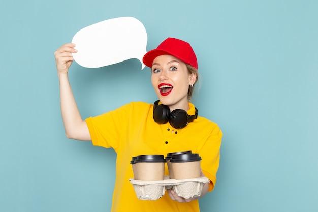 Jovem mensageira feminina de camisa amarela e capa vermelha de frente segurando xícaras de café e uma placa branca no uniforme de trabalho do espaço azul