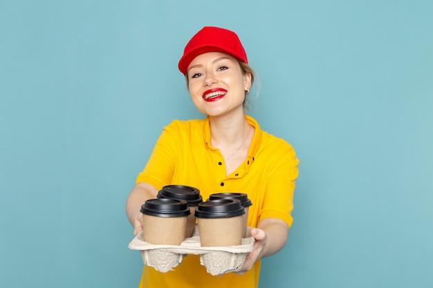 Jovem mensageira feminina de camisa amarela e capa vermelha de frente segurando xícaras de café sorrindo para o trabalhador do espaço azul