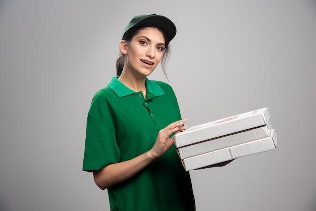 Jovem mensageira posando com caixas de pizza