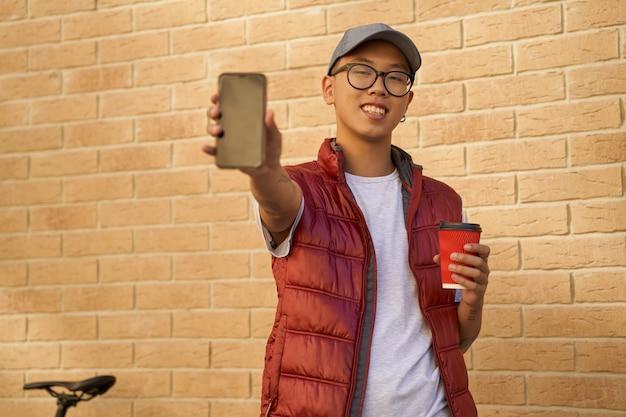Jovem mensageiro asiático alegre com uma xícara de café mostrando scr