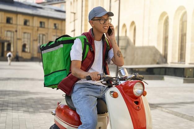 Jovem mensageiro asiático com bolsa térmica falando ao telefone com c