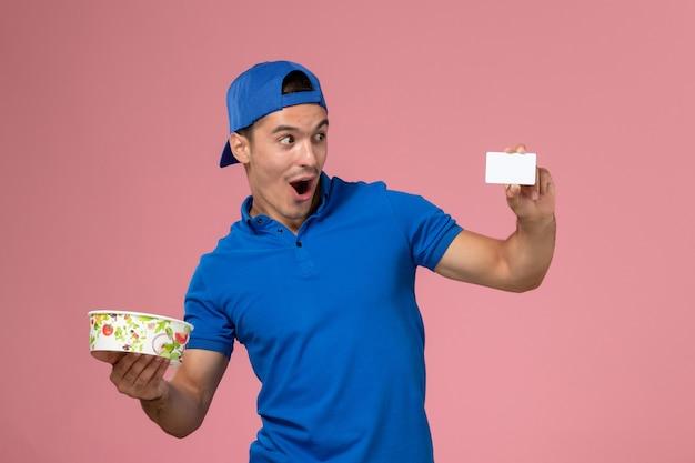 Jovem mensageiro com capa de uniforme azul e vista frontal, segurando um cartão branco e uma tigela de entrega redonda na parede rosa claro