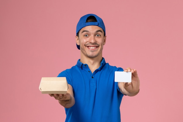 Jovem mensageiro com capa de uniforme azul e vista frontal, segurando um pequeno pacote de comida para entrega e um cartão branco na parede rosa claro