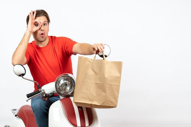Jovem mensageiro confiante de uniforme vermelho sentado na scooter dando uma sacola de papel olhando para algo na parede branca