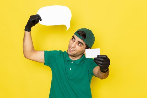 Jovem mensageiro de frente para o homem com uma camisa verde boné verde segurando um cartão branco e uma placa com um sorriso amarelo