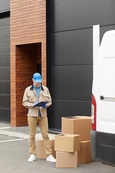 Jovem mensageiro de uniforme fazendo anotações em um documento que está aceitando pacotes ao ar livre perto do armazém
