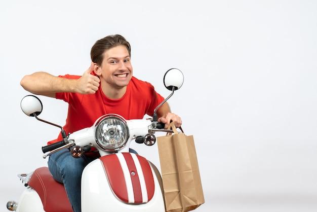 Jovem mensageiro feliz, de uniforme vermelho, sentado na scooter, segurando os pedidos e fazendo um gesto de ok na parede amarela