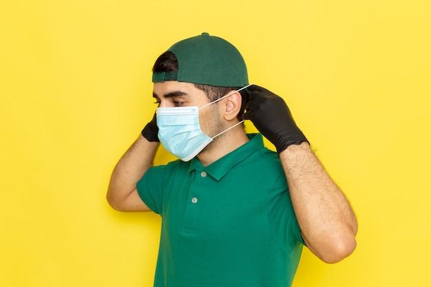 Jovem mensageiro masculino com boné verde de camisa verde e máscara estéril no fundo amarelo, prestando serviço de trabalho em cores