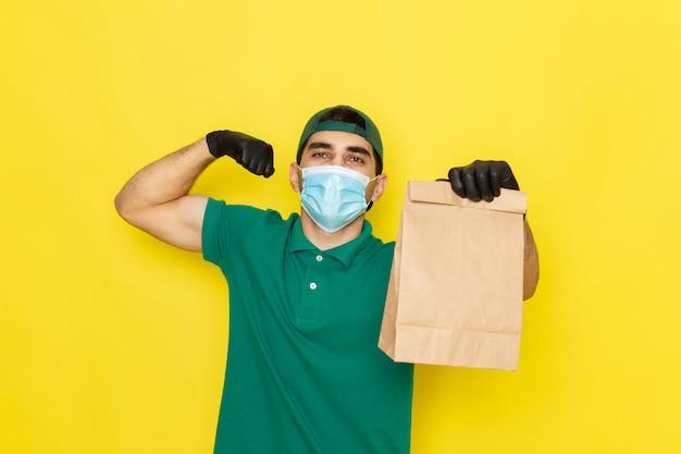 Jovem mensageiro masculino com boné verde de camisa verde segurando o pacote de comida e flexionando em amarelo
