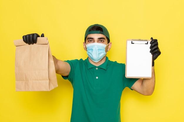 Jovem mensageiro masculino com boné verde de camisa verde segurando o pacote de entrega e o bloco de notas amarelo de frente