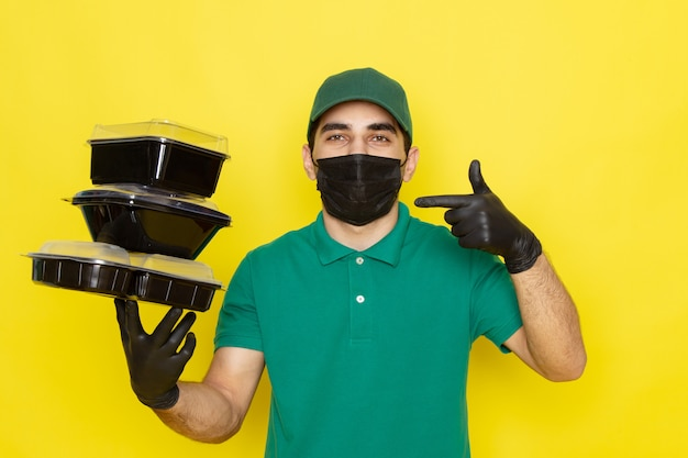 Jovem mensageiro masculino com boné verde de camisa verde segurando tigelas de comida em máscara preta em amarelo