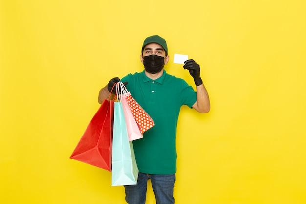 Jovem mensageiro masculino com boné verde de camisa verde segurando uma placa branca e pacotes de compras no fundo amarelo com a cor do serviço de vista frontal
