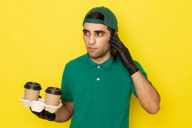 Jovem mensageiro masculino com boné verde de camisa verde segurando xícaras de café e falando no telefone amarelo de frente