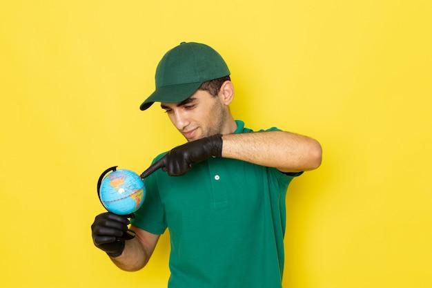 Jovem mensageiro masculino com boné verde e camisa verde segurando o globo terrestre com luvas pretas amarelas
