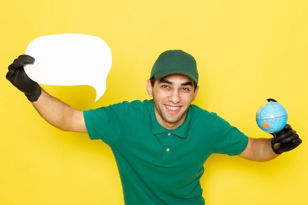 Jovem mensageiro masculino com boné verde e camisa verde segurando um globo e uma placa branca de frente