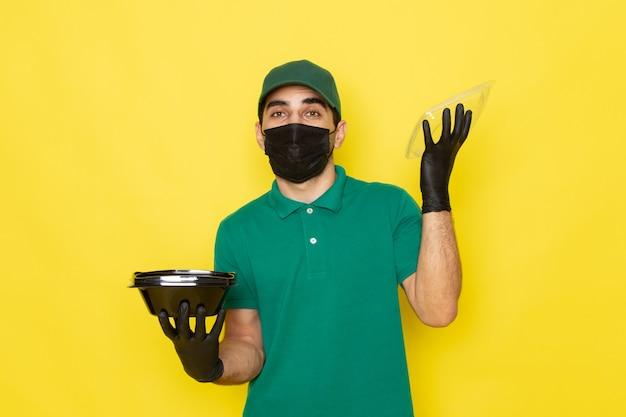Jovem mensageiro masculino com camisa verde e tampa verde abrindo a tigela de comida em máscara estéril preta no fundo amarelo, entregando a cor do serviço.