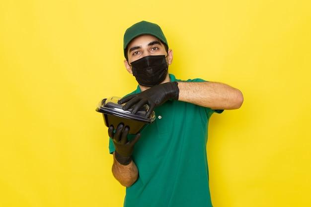 Jovem mensageiro masculino com camisa verde e tampa verde abrindo tigelas de comida em máscara preta no fundo amarelo entregando a cor do serviço.