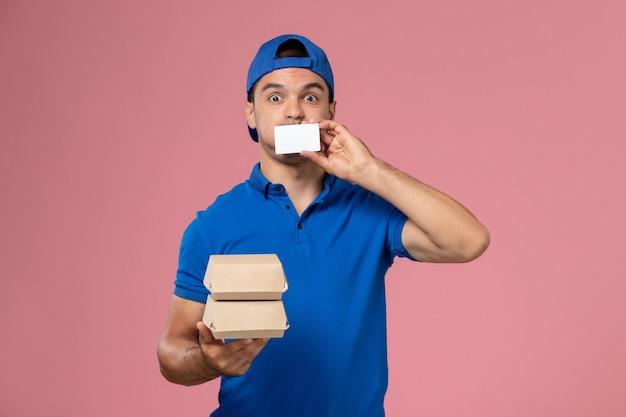 Jovem mensageiro masculino com capa de uniforme azul segurando pequenos pacotes de entrega de comida com cartão na parede rosa claro de frente