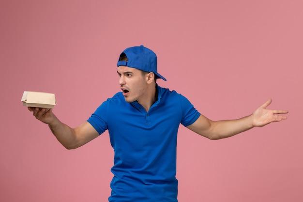Jovem mensageiro masculino com capa de uniforme azul segurando um pacote de entrega de comida na parede rosa