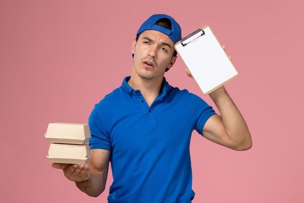 Jovem mensageiro masculino com capa de uniforme azul, vista frontal, segurando pequenos pacotes de comida para entrega com o bloco de notas pensando na parede rosa claro