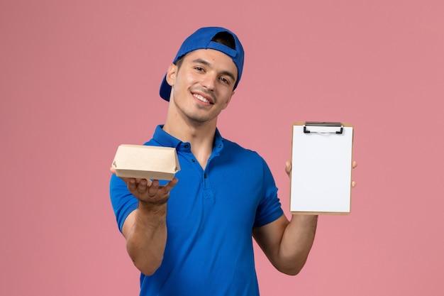 Jovem mensageiro masculino com capa de uniforme azul, vista frontal, segurando um pequeno pacote de comida para entrega e um bloco de notas com um sorriso na parede rosa claro