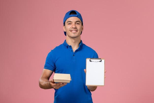 Jovem mensageiro masculino com capa de uniforme azul, vista frontal, segurando um pequeno pacote de comida para entrega e um bloco de notas na parede rosa claro