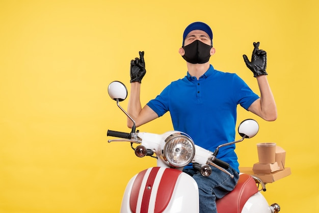 Jovem mensageiro masculino de frente para a bicicleta na máscara sobre fundo amarelo