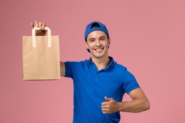 Jovem mensageiro masculino de uniforme azul e capa com pacote de papel de entrega nas mãos, sorrindo na parede rosa